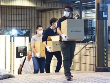 犯行グループが拠点としていたビジネスホテルを家宅捜索し、押収物を運び出す県警の捜査員ら=22日午後6時40分ごろ、東京都豊島区内