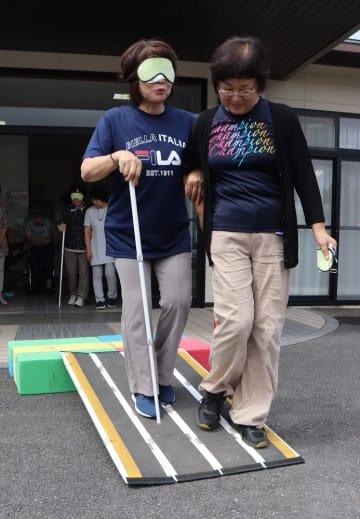 段差や坂道での介助方法を学ぶ参加者=雲仙市小浜町
