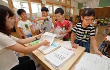 笑顔で夏休みの宿題を提出する児童(26日午前9時52分、京都市右京区・西京極小)※写真の一部を加工しています。