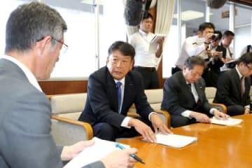 柏崎市の桜井雅浩市長(左)が求めていた廃炉計画の回答を伝える東京電力の小早川智明社長(中央)=26日、柏崎市役所