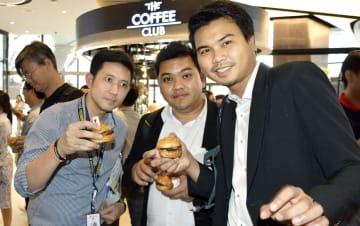 秋田牛PRイベントで、ハンバーガーを食べる男性ら=26日、バンコク(共同)