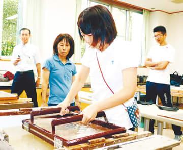 和紙をすき、卒業証書を作る石井教諭(右から2人目)と高島教諭(同3人目)ら