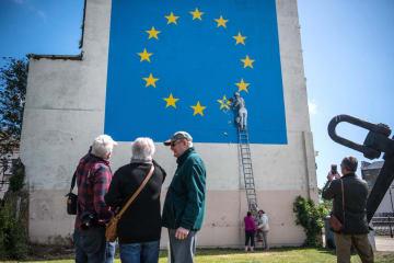 EUの旗から星の一つを消そうとする作業員を描いた壁画。バンクシーの作品=2017年5月、ドーバー(ゲッティ=共同)