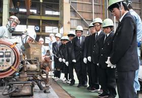 楢﨑製作所の現場を興味津々に見学する中学生