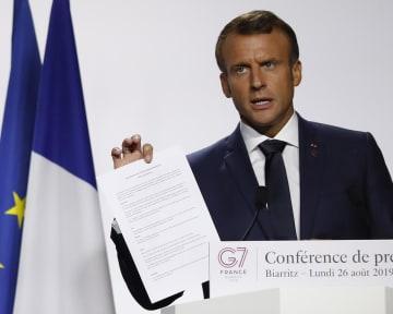 26日、G7サミット閉幕後の記者会見で合意文書を持つフランスのマクロン大統領=フランス・ビアリッツ(AP=共同)