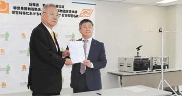 覚書を締結した玉井理事長(左)と田中局長。右奥にあるのが臨時災害放送局用の設備