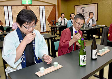 新潟県・庄内エリアDCに向け、各旅館で提供する飲み比べセットの県産酒を試飲して選ぶ参加者=南陽市・丹泉ホテル