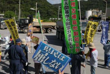 次々と土砂を搬入する大型車両に向かって抗議する市民=27日午前9時半ごろ、名護市安和