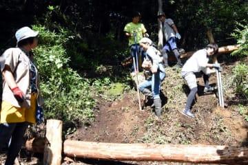 三陸駒舎の裏山の斜面を活用し、大きな滑り台の土台作りに励む参加者