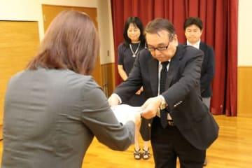【末松市長(手前)に報告書を手渡す藤原会長=鈴鹿市神戸2丁目の市男女共同参画センターで】