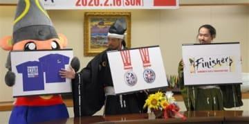 お披露目された熊本城マラソン第9回大会の参加賞のデザイン。左側からTシャツ、フル完走者向けのメダル、タオル=熊本市役所