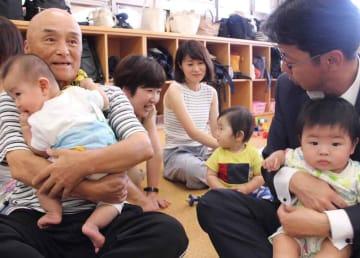 赤ちゃんを抱っこして、子育て支援イベントの手助けをする民生児童委員や、体験に訪れた中小路市長(京都府長岡京市神足3丁目・エンゼル)