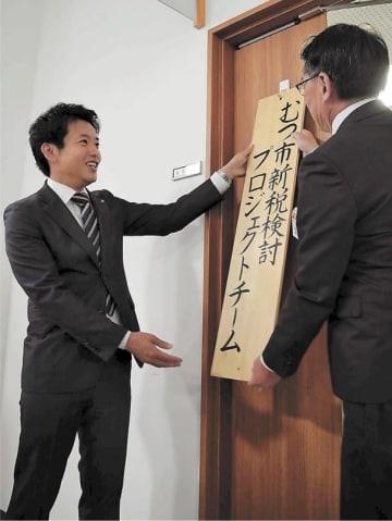 独自課税に向けて立ち上げた検討チームの看板を掛ける宮下市長(左)=27日、むつ市役所