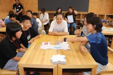ロボット「アリロ」を指定した方向に動かすための設定を話し合う子どもたち=佐世保市、九州文化学園小中学校