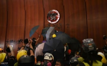 Protesters, protected from cameras by overlapping umbrellas, deface the emblem of Hong Kong. Photo: Thammakhun John Crowcroft/HKFP.