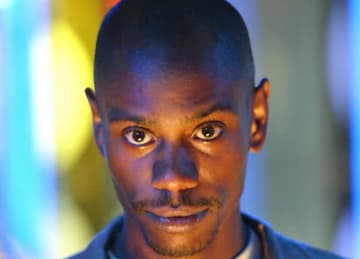 NEW YORK - SEPTEMBER 8: (U.S. TABS OUT) Comedian Dave Chappelle appears on stage during MTV's Total Request Live at the MTV Times Square Studios September 8, 2003 in New York City. (Photo by Scott Gries/Getty Images)