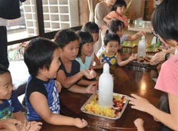 噴き出す炭酸飲料のペットボトルに驚く子どもたち=多良木町