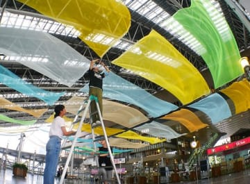「時空の広場」に色とりどりの布を装飾する学生=28日、JR大阪駅