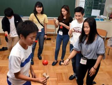 児童とけん玉に挑戦し日本の文化を体験するホン・チョンさん(右)ら
