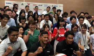 神戸製鋼の社員とともに記念撮影におさまる、ラグビー日本代表ワールドカップメンバーのアタアタ・モエアキオラ(写真下、左から2人目)と山中亮平(写真下、右)の両選手(神戸製鋼コベルコスティーラーズ)。神戸製鋼本社にて(写真:ラジオ関西)