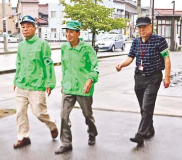 夏休み期間に合わせ、他の補導員と一緒に滑川市街地を見回る野島さん(中央)