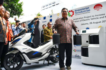 Indonesia's Industry Minister Airlangga Hartarto poses with e-scooter batteries at a launch event for an experimental trial of e-bike and battery station operation in Jakarta on Aug. 28.