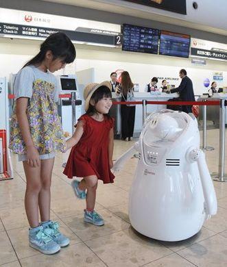 チェックインカウンターの近くで子どもたちと会話するアバターロボット=29日、益城町