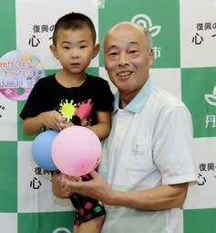 由良英士ちゃん(左)が飛ばした風船を届けた高田和美さん=丹波市市島町上田、丹波市役所市島支所