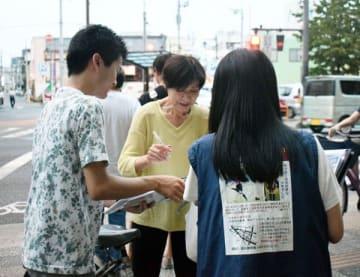 情報提供を呼び掛ける母親(右)。ビラ配りには孝徳君の同級生(左)も参加した=8月、熊谷市内
