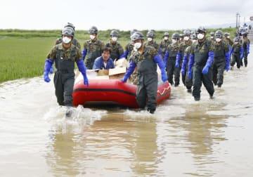 冠水した佐賀県大町町の道路を、ボートを引いて進む自衛隊員=30日午前9時29分
