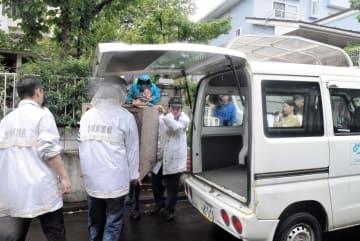 捕獲したクマを入れた木箱を運び出す警察官=30日午後1時30分ごろ、仙台市泉区加茂2丁目