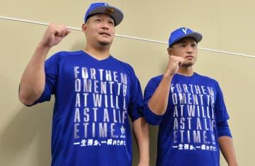 終盤戦のチームスローガンがプリントされたTシャツを着る筒香(左)と石田