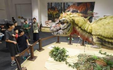 リアルな動きを見せるティラノサウルスの生体ロボットに見入る入場者