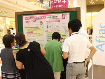 がんに関するパネル展示を見る買い物客ら=30日、さいたま市中央区のイオンモール与野