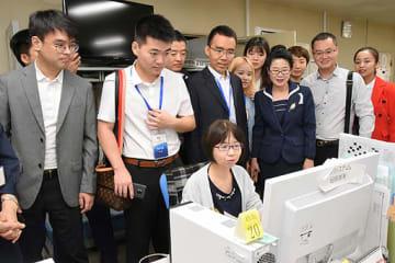 特別号外の製作現場を見学する中国訪問団=30日、鳥取市富安2丁目の新日本海新聞社