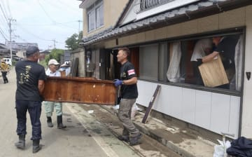 大雨による浸水被害を受けた佐賀県大町町の住宅から家具を運び出すボランティア=31日午前