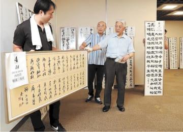企画・運営委員の指導で進められた展示作業=30日、仙台市宮城野区のTFUギャラリーミニモリ