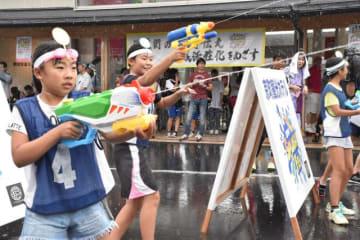 温泉水を詰めた水鉄砲を撃ち合う参加者たち