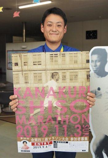 「金栗四三翁マラソン大会」のポスターを持つ和水町職員=同町