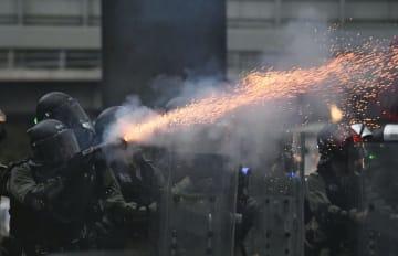 香港立法会周辺で、デモ隊の若者らに向けて催涙弾を発射する警官隊=31日(共同)