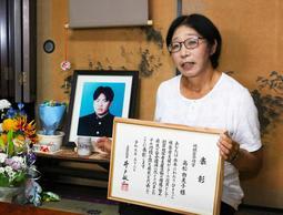 聡至さんの遺影に、功労者の表彰状を見せる高松由美子さん=兵庫県稲美町印南