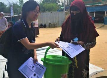 ロヒンギャの女性にバケツに入った生理用品を手渡すJADEのスタッフ=バングラデシュ・コックスバザール(田中洋人さん提供)