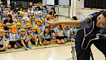 女性警官(右)と一緒に指さし確認を練習する子どもたち