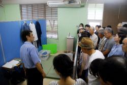 模擬単独居室を見ながら入院中の生活について説明を聞く参加者たち(京都府宇治市)