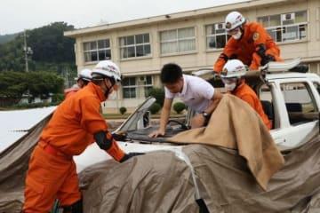 訓練で車両から助け出される要救助者