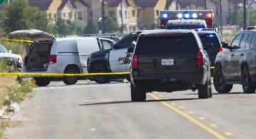 8月31日、米南部テキサス州オデッサで、乱射事件後に車両(左奥)を取り囲む警察(Midland Reporter―Telegram提供・AP=共同)