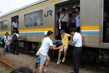 はしごを使わず電車から降りる訓練参加者=横浜市鶴見区のJR鶴見線浅野駅~新芝浦駅間
