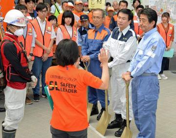 ボランティアセンター運営訓練で、スコップを手に、スタッフの説明に耳を傾ける(右から)安倍首相、森田知事、松戸市長