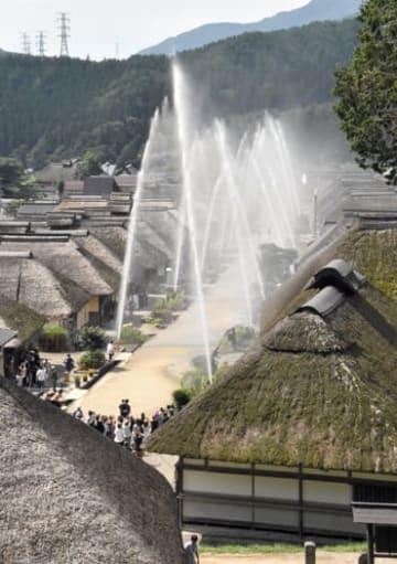 大内宿で行われた防災放水訓練で、かやぶき屋根の集落に放たれる水の幕