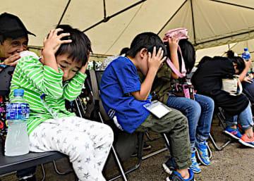 頭を抱えて地震の揺れから身を守る子どもたち=1日、大阪府吹田市の千里北公園
